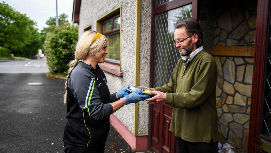 Eine freiwillige Helferin übergibt einem Nachbarn ihrer Gemeinde an der Haustür eine warme Mahlzeit