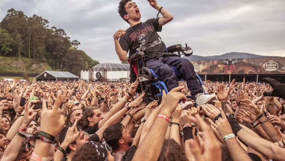 """Besucher des spanischen """"Resurrection Fest"""" heben einen jungen Mann im Rollstuhl in die Höhe"""