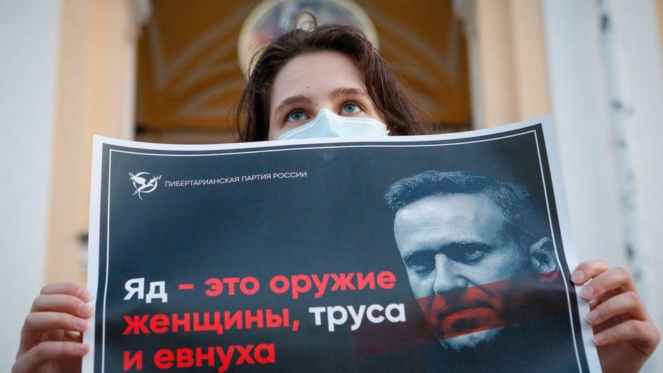 """Demonstrantin mit Plakat in Sankt Petersburg: """"Gift ist die Waffe einer Frau, eines Feiglings und eines Eunuchen!"""""""
