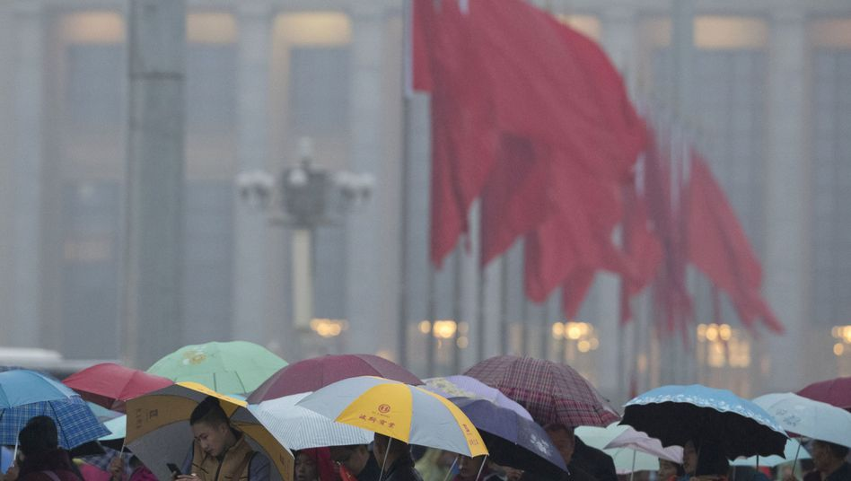 Touristen mit Regenschirmen auf dem Tian'anmen-Platz in Peking, während in der Großen Halle des Volkes der 19. Parteitag der Kommunistischen Partei Chinas stattfindet.