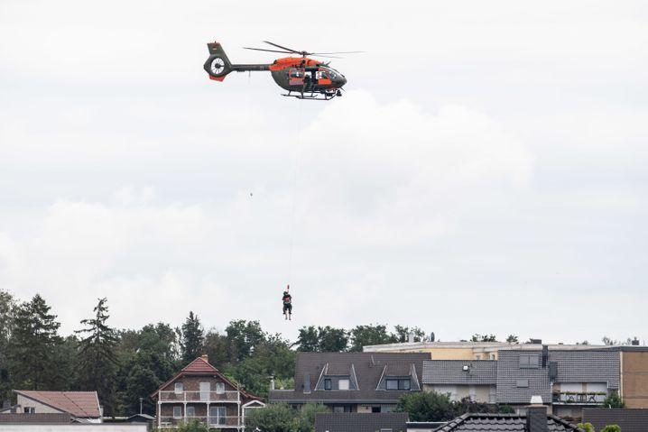 Mit Hilfe einer Seilwinde werden Menschen per Hubschrauber aus dem Ortsteil Heimerzheim gerettet
