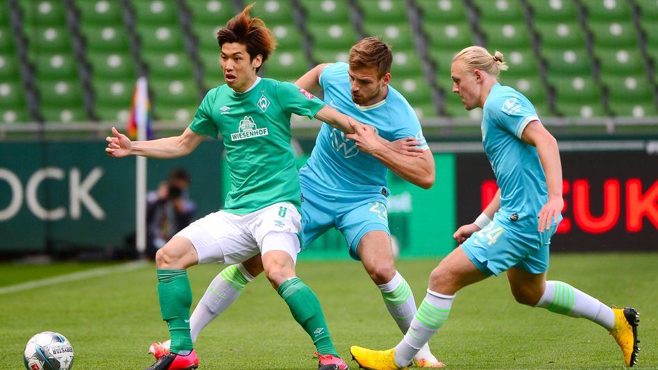 Bremens Yuya Osako im Zweikampf mit den Wolfsburgern Marin Pongracic und Xaver Schlager (von links)