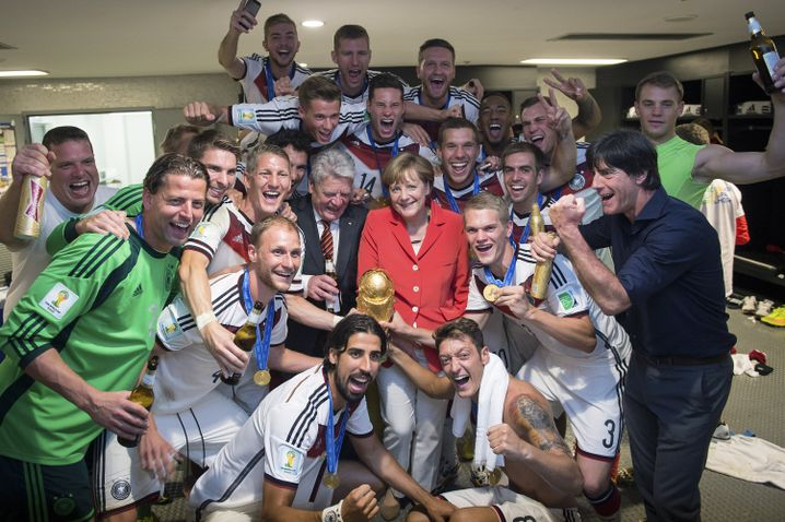 German Chancellor Angela Merkel with the German team after it won the 2014 FIFA World Cup.