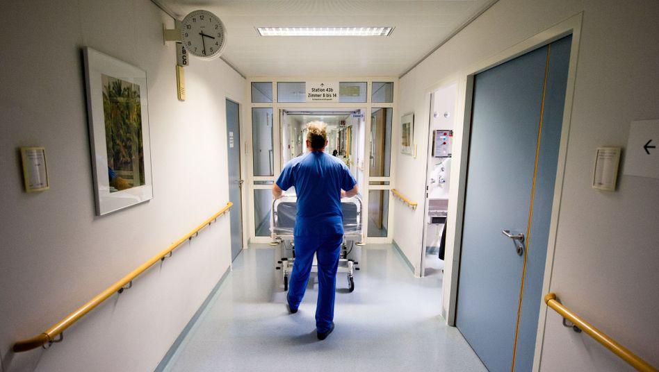 Ein Krankenpfleger schiebt in einer Klinik ein Krankenbett durch den Flur