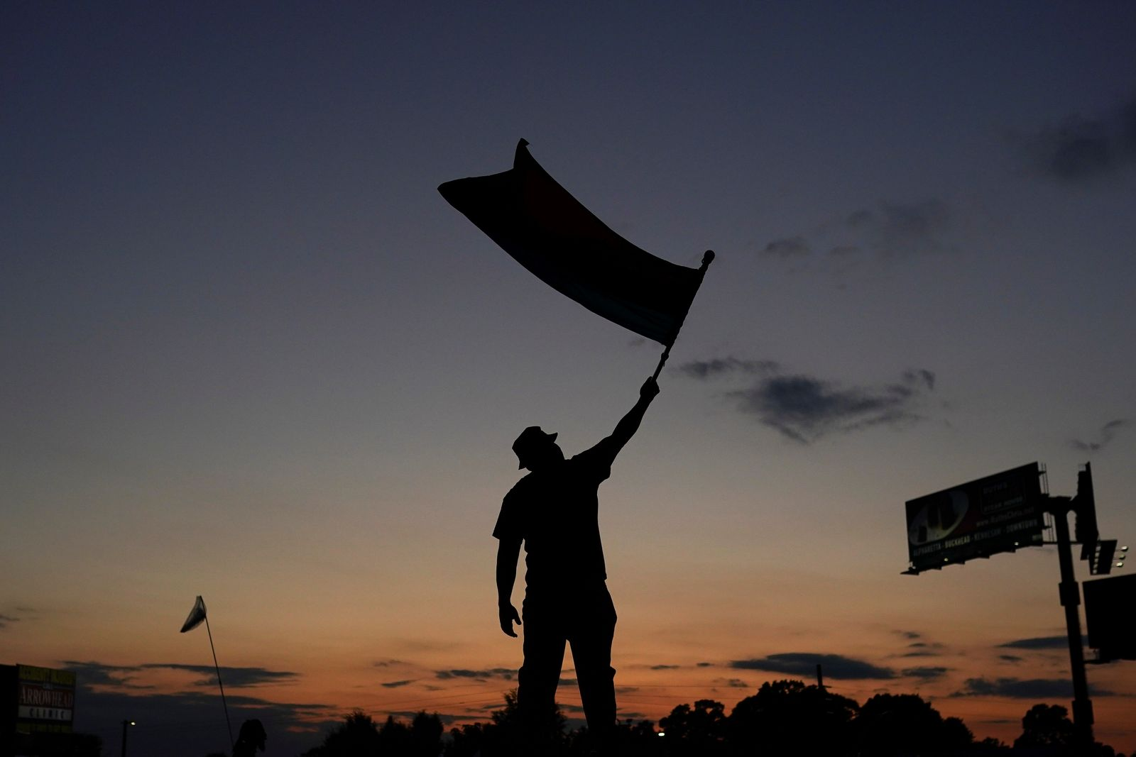 A protester is seen in silhouette waving a flag while blocking traffic on a freeway during a rally against racial inequality and the police shooting death of Rayshard Brooks, in Atlanta