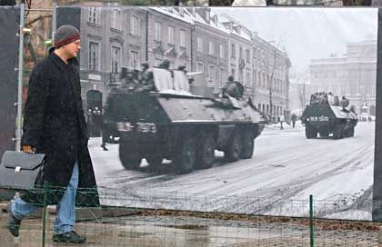 Poland just marked the 25th anniversary of the 1981 imposition of martial law. Here, a young man in Warsaw walks past a photo documenting the event.