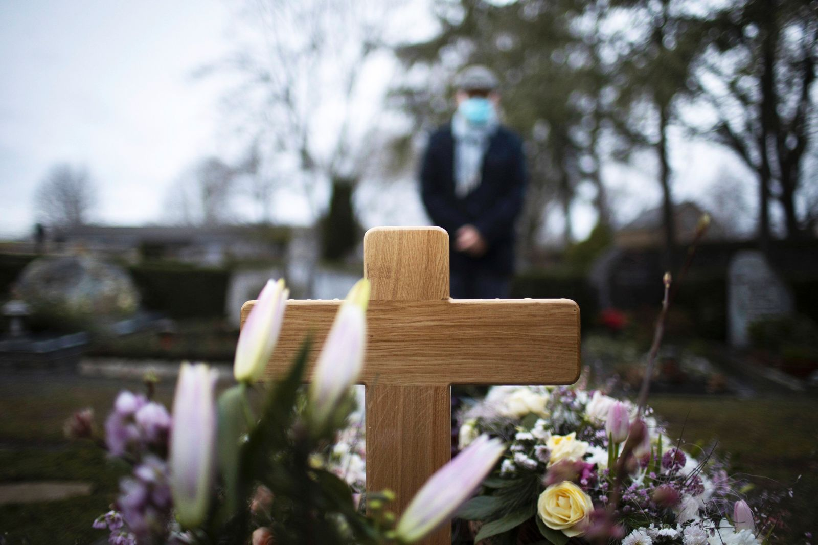 Bonn, Germany - January 21: In this photo illustration Man with a mouth-nose mask stands in front of a grave on January