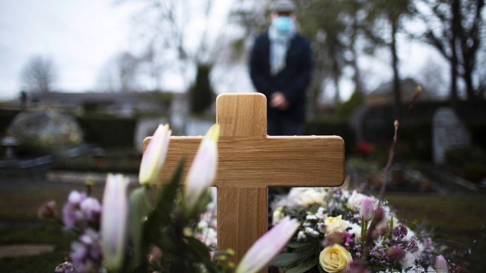 Ein Mann mit einer Mund-Nasen-Maske steht vor einem Grab (Symbolbild)