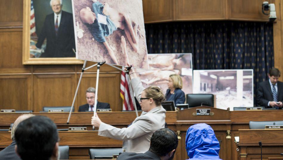 "Fotograf ""Caesar"" (mit blauer Kapuze) bei Präsentation im US-Kongress 2014:Vermisste Söhne, Väter, Brüder, Ehemänner"