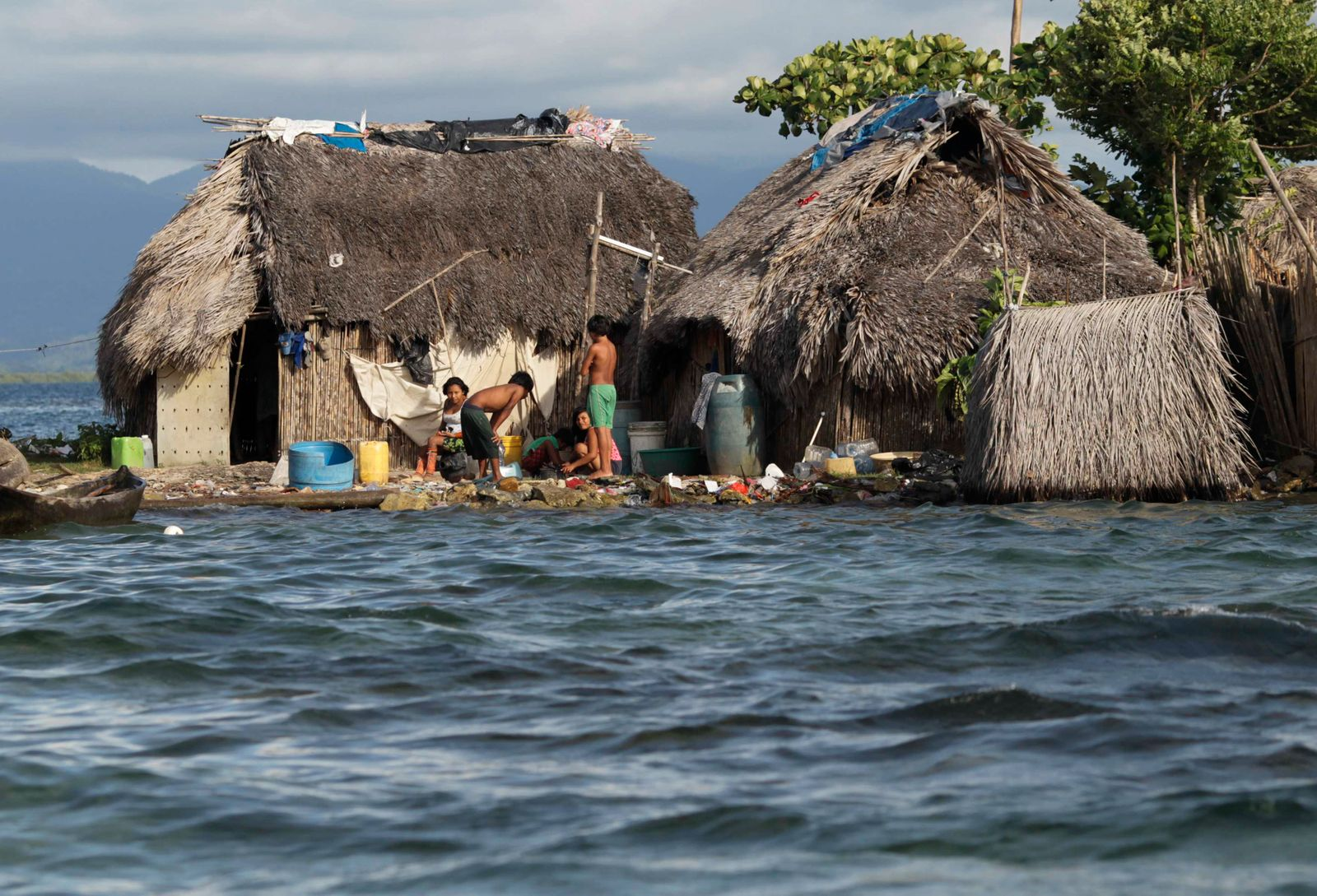 Indigenous Guna residents stand outside a house in Carti Sugdub island at the Comarca of Kuna Yala