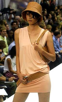Das sportlich-legere Jersey-Kleid mit V-Ausschnitt von Kenneth Cole wird durch den breiten Hüftgürtel geschmückt. Dazu passend Hütchen und Handtasche
