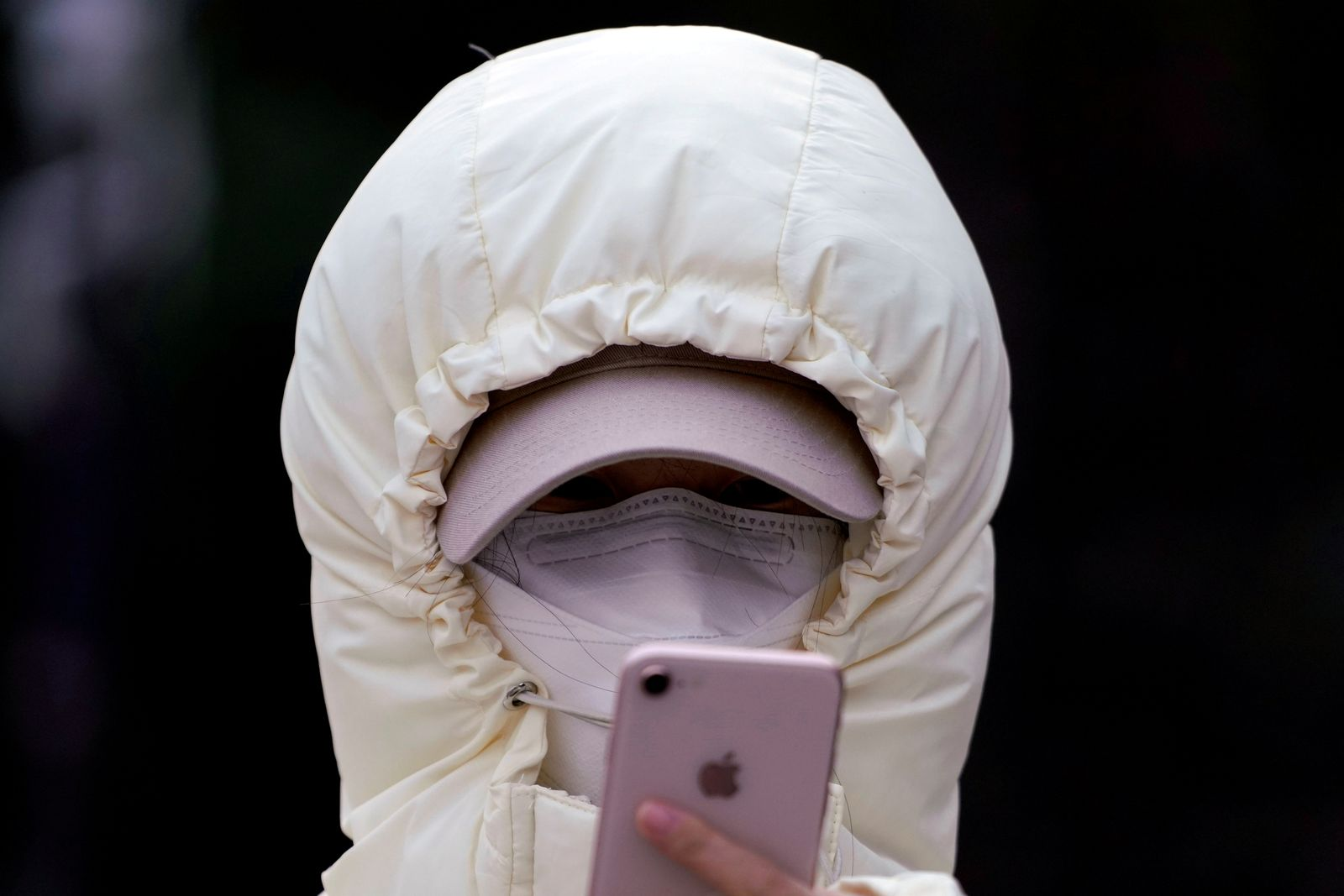 FILE PHOTO: A woman wearing a mask checks her mobile phone in Shanghai
