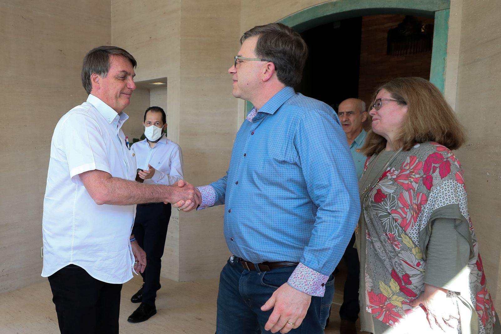 Brazil's President Jair Bolsonaro greets U.S. Ambassador Todd Chapman during a meeting in Brasilia