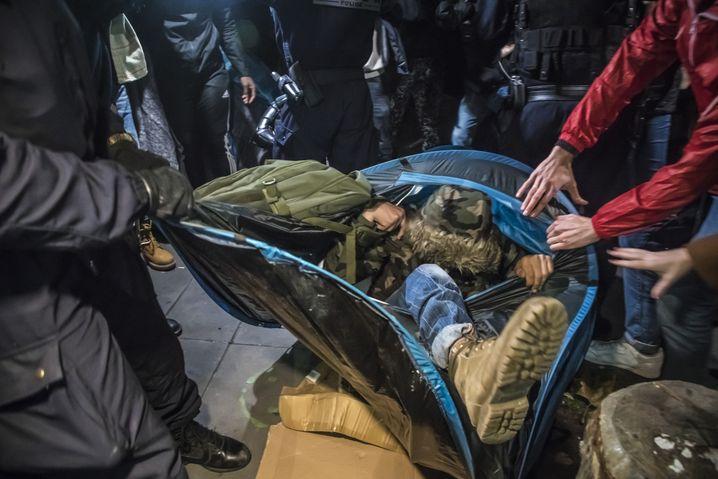 Ein Flüchtling wird in seinem Zelt weggetragen.