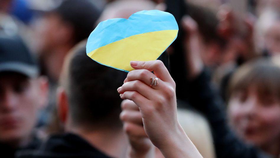 Eine Anhängerin von Petro Poroschenko hält ein Herz in den Farben der Ukraine hoch
