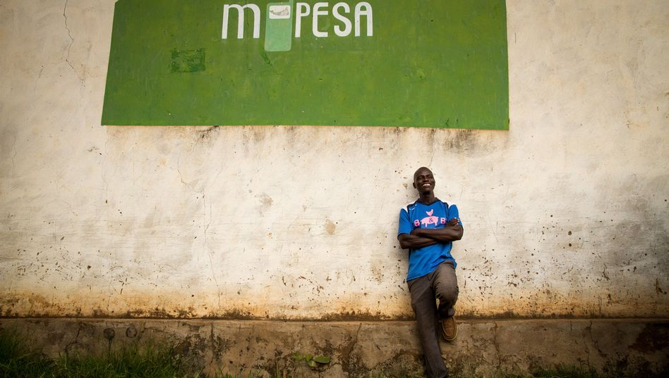 Erick Odhiambo stands in front of an advertisement for M-Pesa.