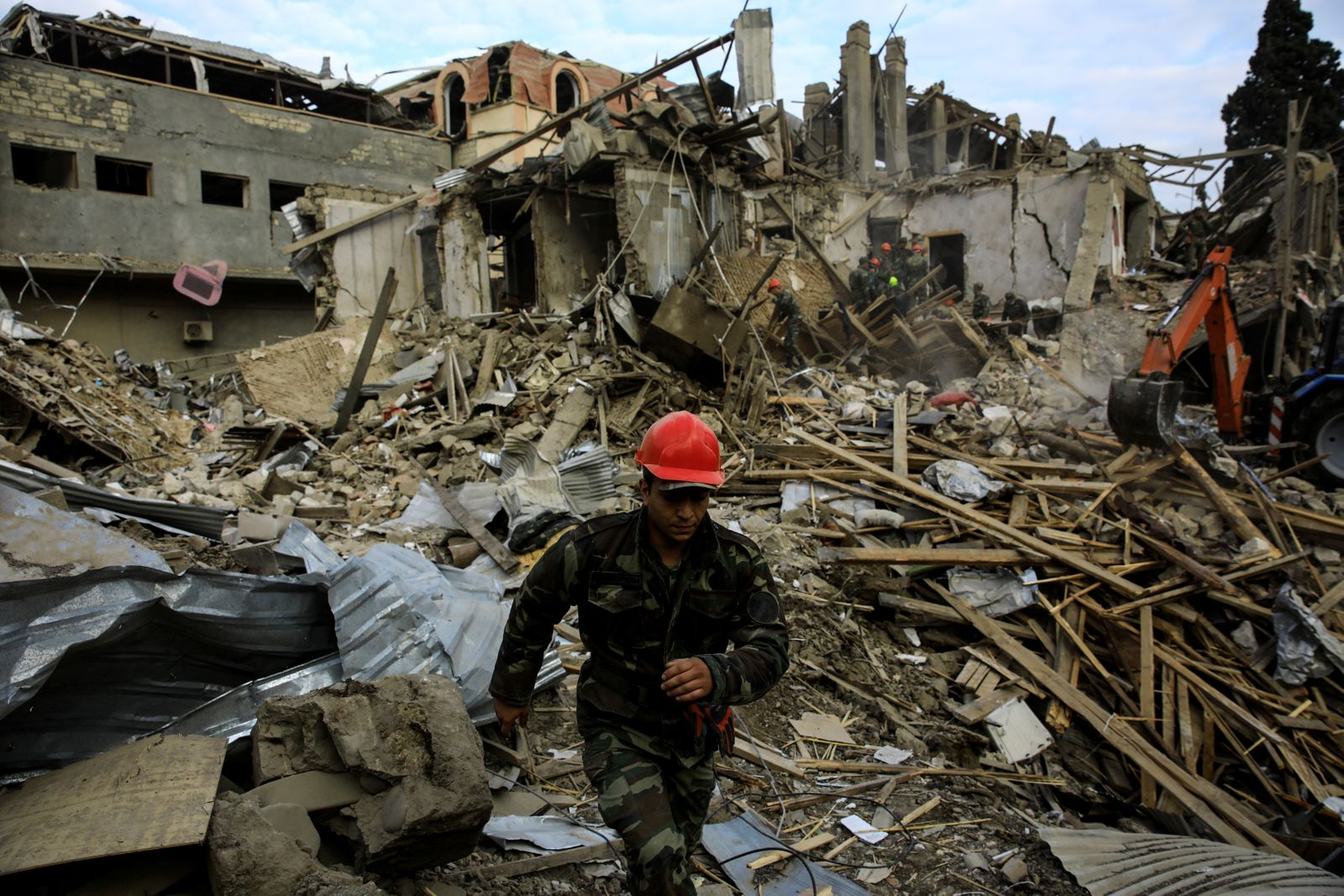 Search and rescue teams work on the blast site hit by a rocket during the fighting over the breakaway region of Nagorno-Karabakh in the city of Ganja