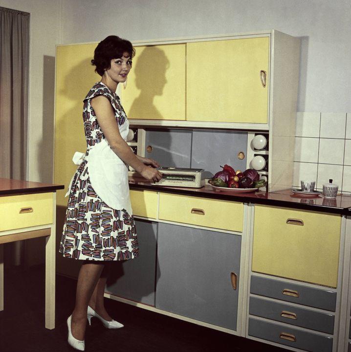 Die moderne Küche ist auch im Sozialismus ein Traum. Die um 1960 entstandene Aufnahme inszeniert das herkömmliche Rollenklischee.