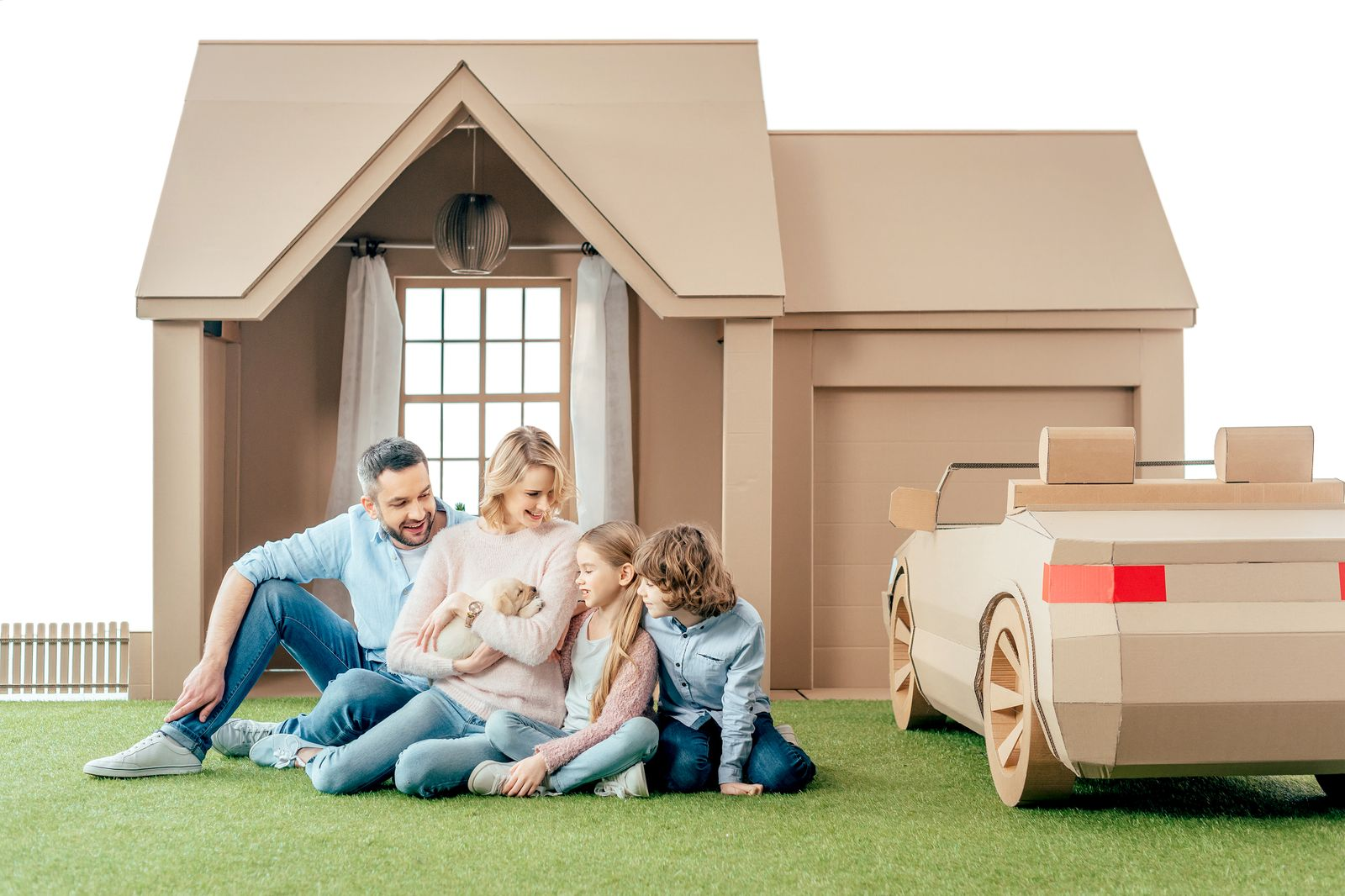 happy young family sitting on yard of cardboard house with their puppy isolated on white