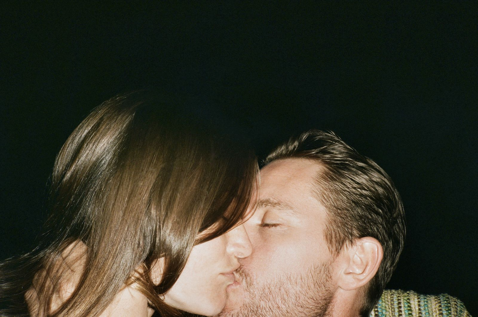 Close-up of affectionate couple kissing against black background