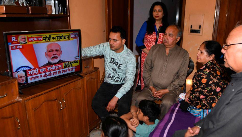 Indische Familie während Modis Fernsehansprache in Amritsar