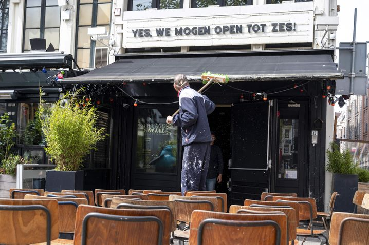 Ein Restaurantangestellter in Amsterdam bereitet die Terrasse für die Öffnung vor