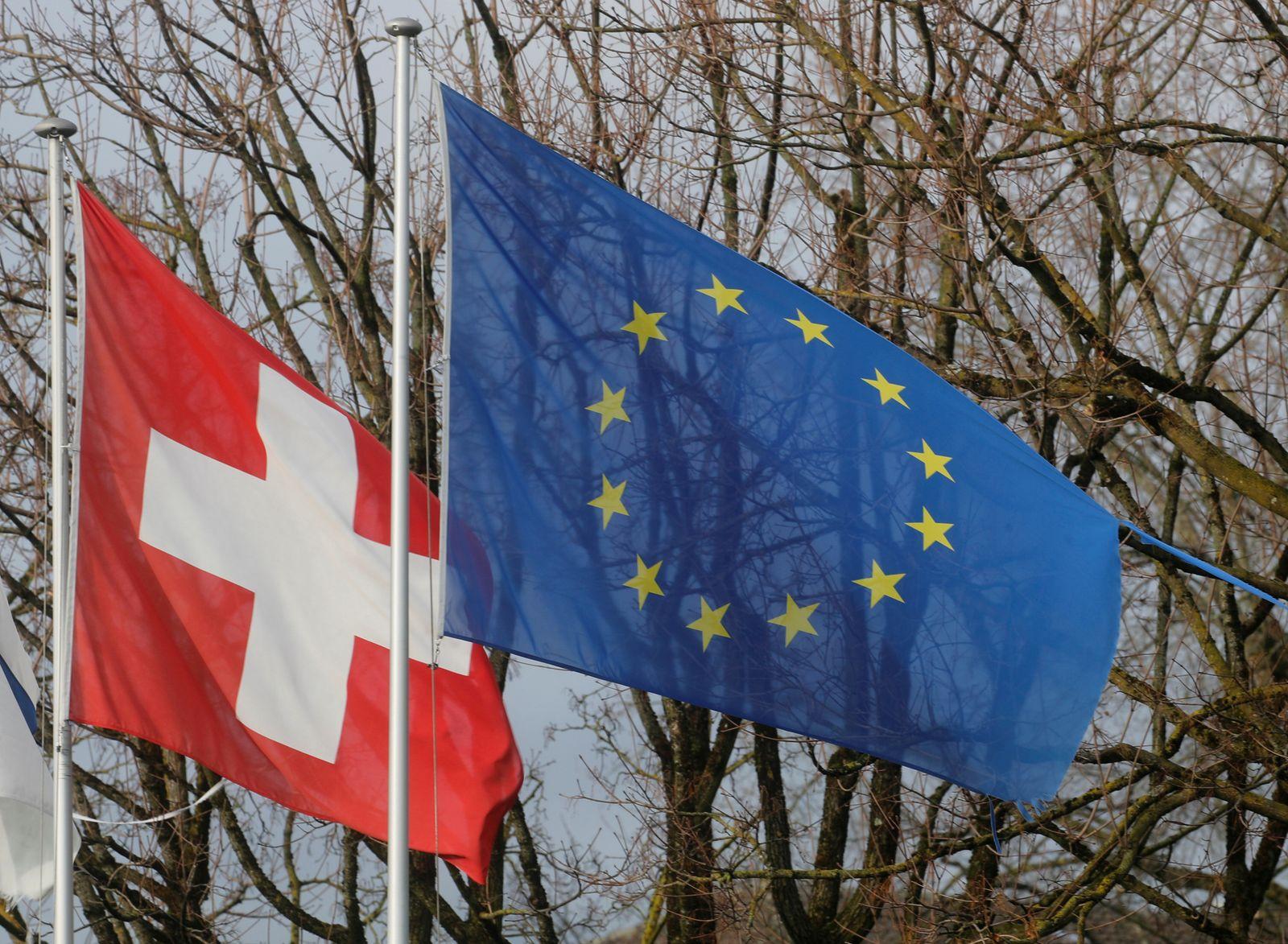 FILE PHOTO: Switzerland's national flag flies beside the one of the European Union in Steinhausen