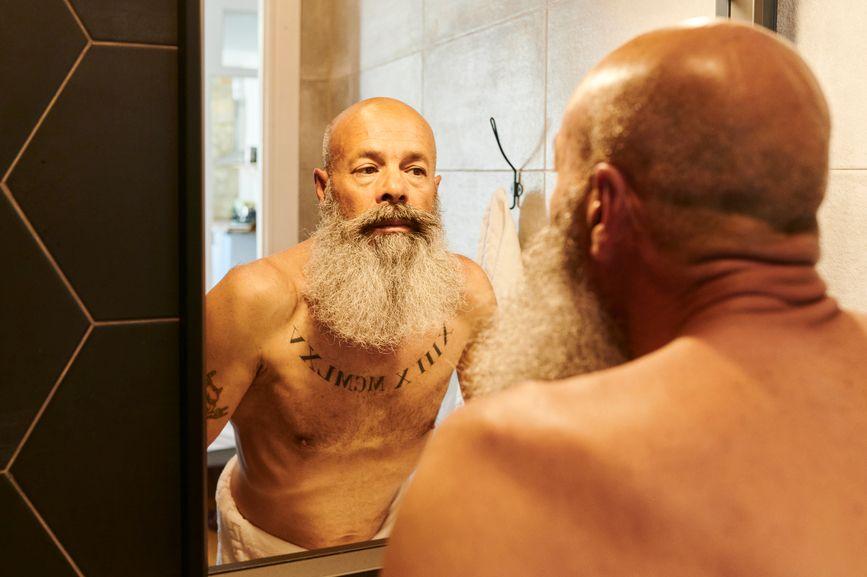 Mature Man Looking In His Bathroom Mirror