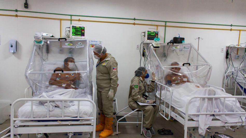 Brasilien, Manaus: Krankenpfleger unterhalten sich mit Patienten auf der Intensivstation im Feldlazarett Gilberto Novaes.
