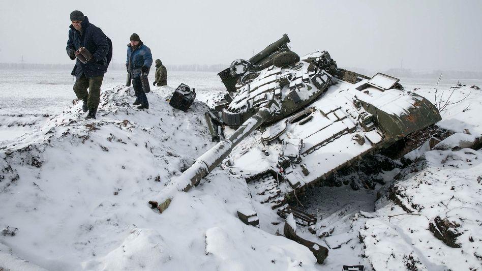 Separatisten weiden einen zerstörten Panzer der ukrainischen Armee aus. Aufgenommen bei Debalzewe, 16. Februar