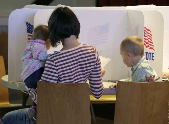 Frau mit ihren Kindern beim Wählen