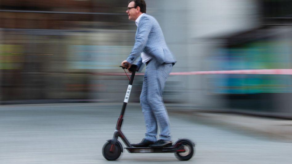 Ein Mann fährt mit einem E-Tretroller eines US-amerikanischen E-Scooter-Sharing-Anbieters