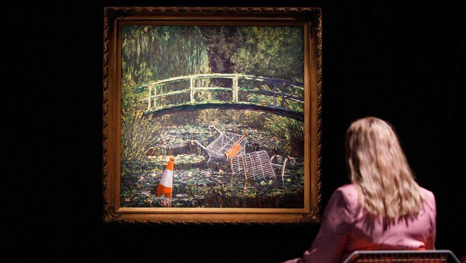 Galeriemitarbeiterin betrachtet Banksy-Gemälde