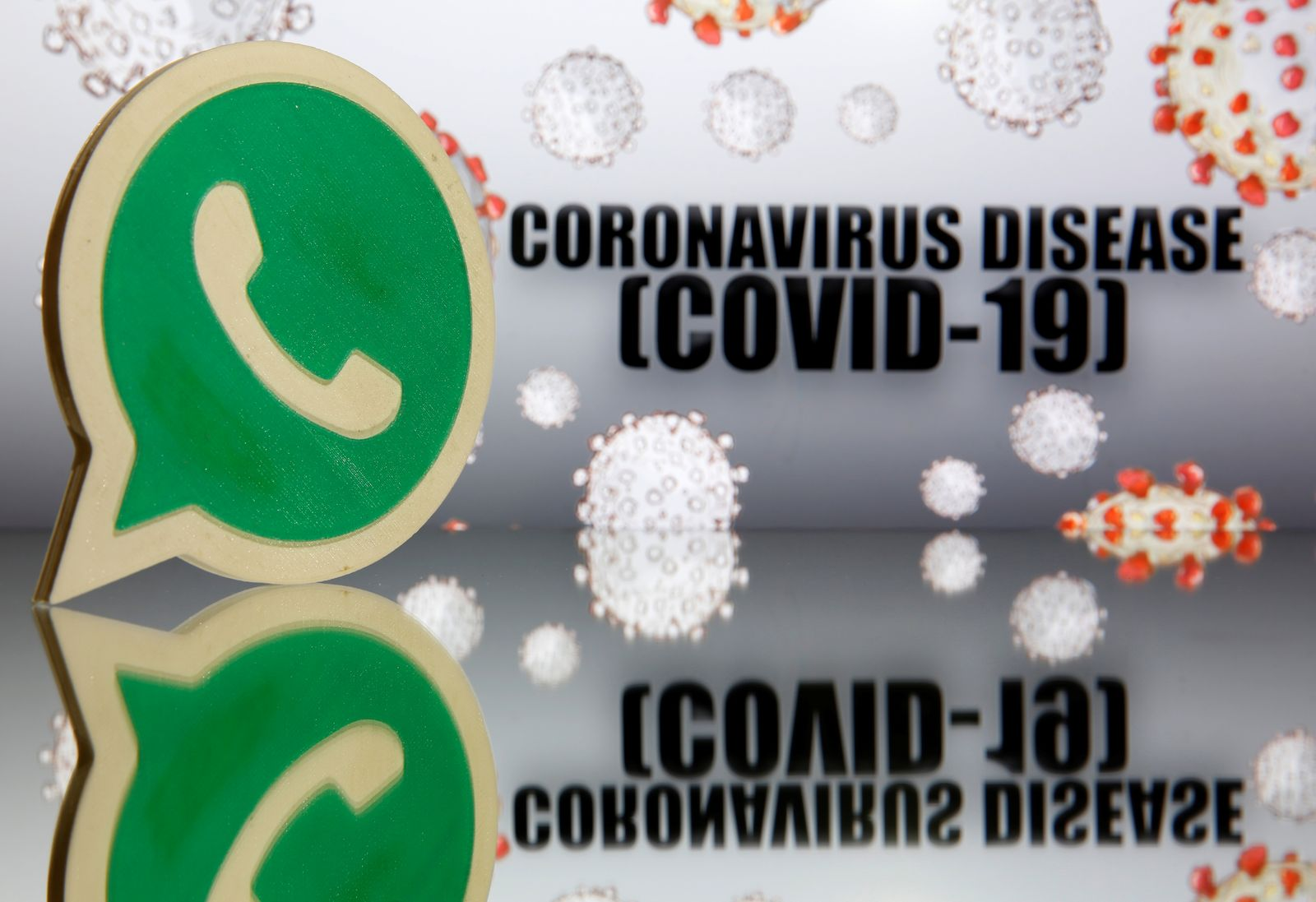 A 3D-printed Whatsapp logo is seen in front of displayed coronavirus disease (COVID-19) sign