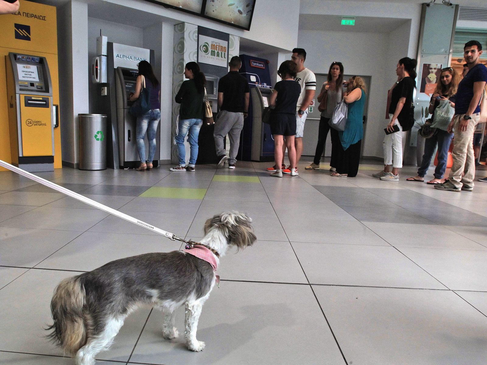 People queue at ATM to withdraw money in Athens