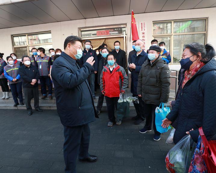 Chinas Präsident Xi Jinping mit Atemmaske im Gespräch mit Bürgerinnen und Bürgern.