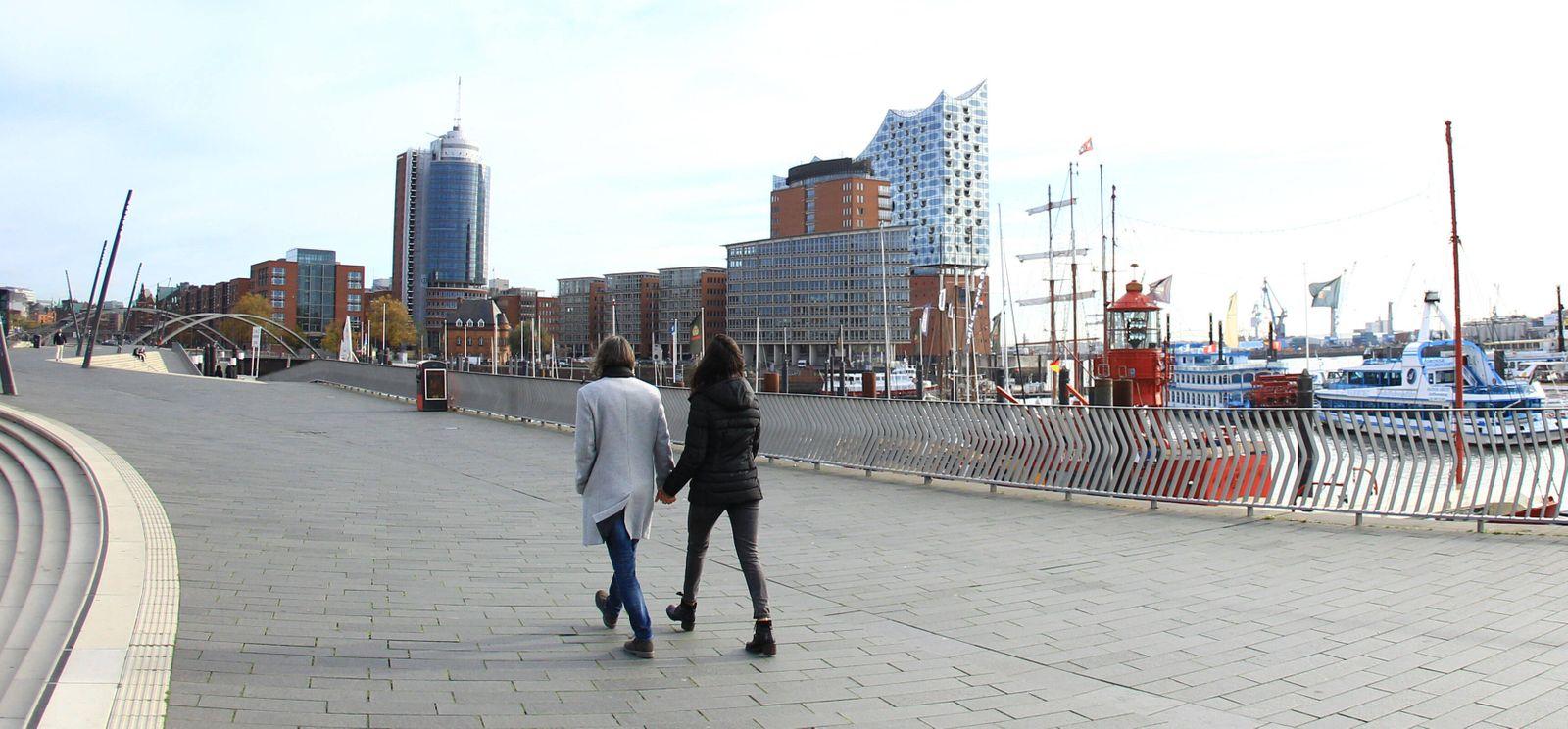 Zwei Menschen schlendern auf der Hamburger Hafenpromenade entlang. Wegen des Lockdowns ist der sonstige Touristen-Hotsp