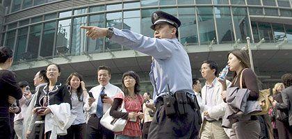 Ein Polizist instruiert Menschen, die aus einem Gebäude in Shanghai evakuiert wurden. Die Erschütterungen des Erdbebens waren noch tausende Kilometer entfernt zu spüren.
