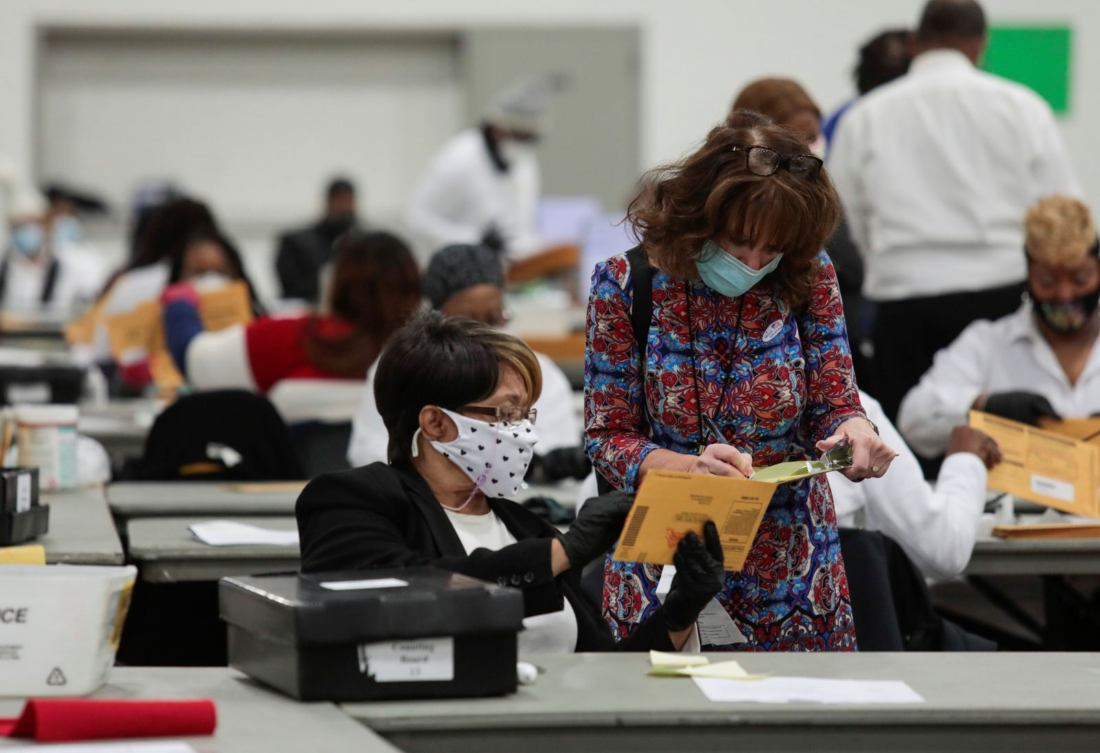 A poll challenger looks at absentee ballots to be counted on election day being processed by poll workers, at the TCF Center in Detroit, Michigan