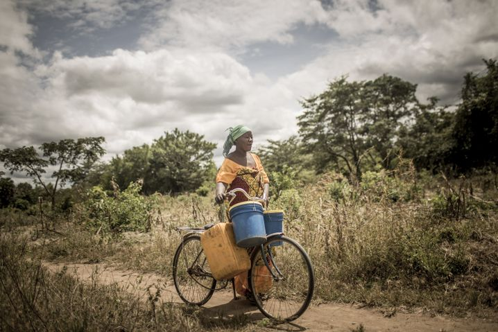 Aisha Bahari walks her bicycle to a pump station to fetch water.