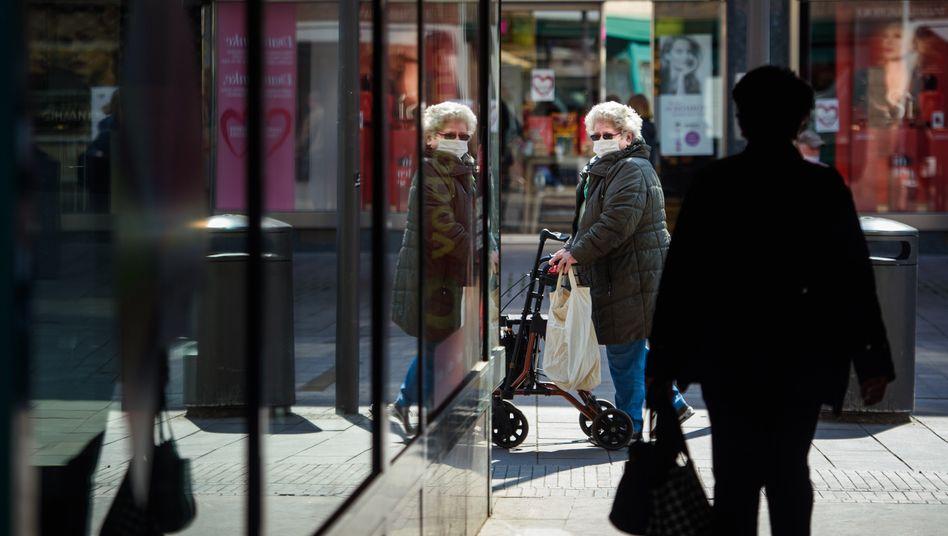 Eine ältere Frau trägt beim Einkauf Mund-Nasen-Schutz