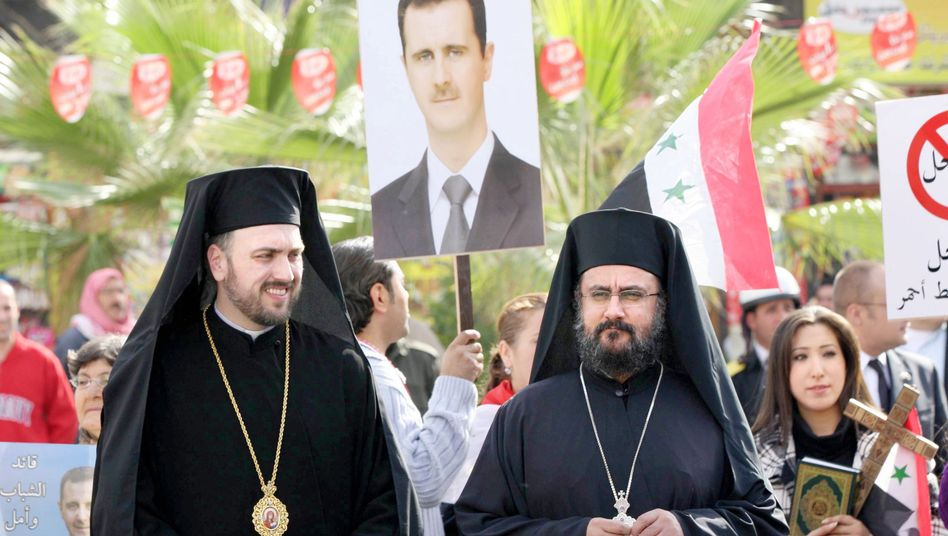 Two Syrian Orthodox priests wait for the arrival of Russian Orthodox Patriarch Kirill in Damascus on Nov. 12, 2011. A poster of President Bashar Assad can be seen in the background.