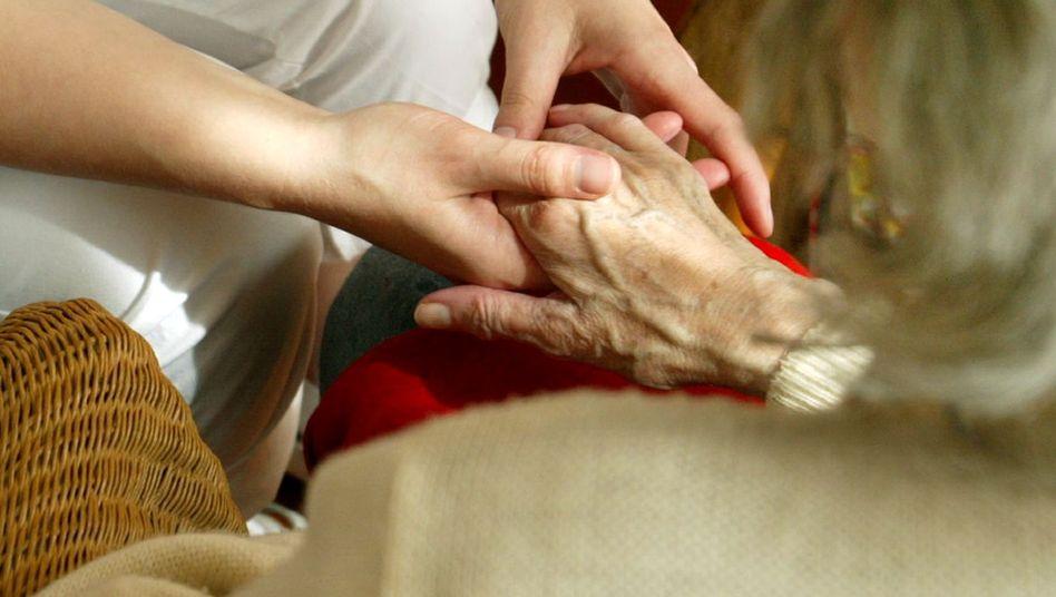 """Eine Schwester hält die Hand einer Patientin: """"Verbesserung der Lage ist nicht abzusehen"""""""