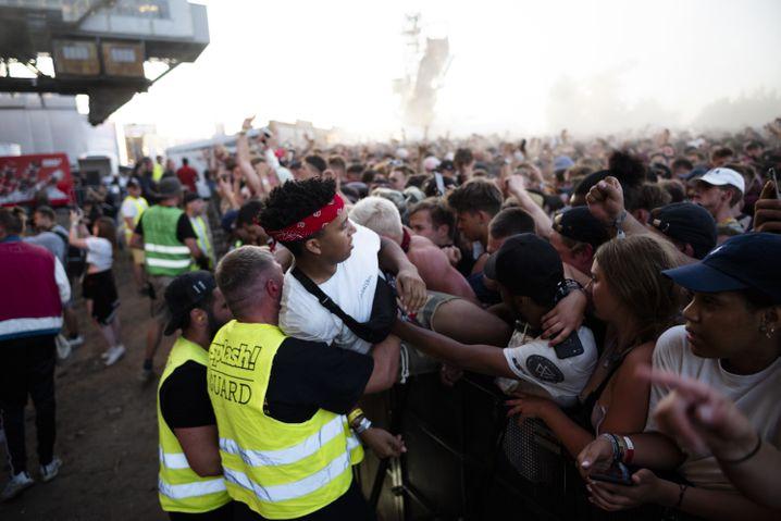 06.07.2018, Sachsen-Anhalt, Gräfenhainichen: Helfer ziehen Fans beim internationale Hip-Hop- und Reggae-Festival aus dem Gedränge vor der Bühne. Seit 2009 findet auf der Halbinsel des ehemaligen Tagebau das dreitägige Musikfest statt. Foto: Alexander Prautzsch/dpa-Zentralbild/dpa +++ dpa-Bildfunk +++ | Verwendung weltweit