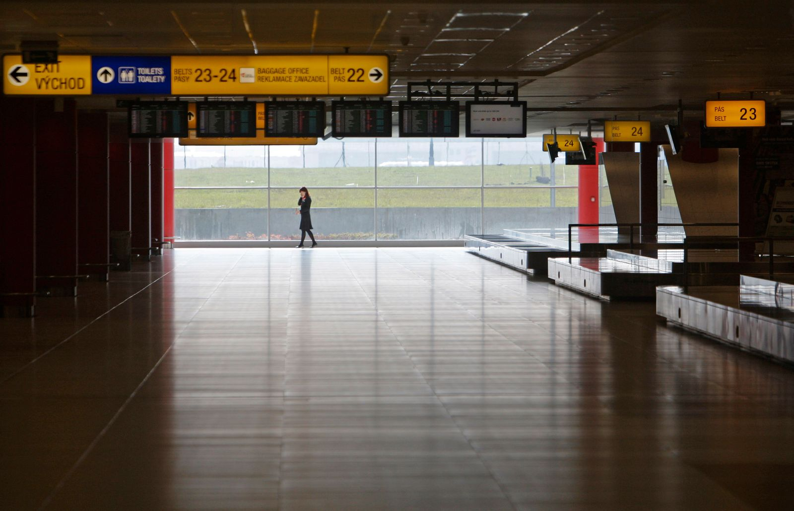A woman makes a phone call in empty arrival hall of Prague's Ruzyne Airport