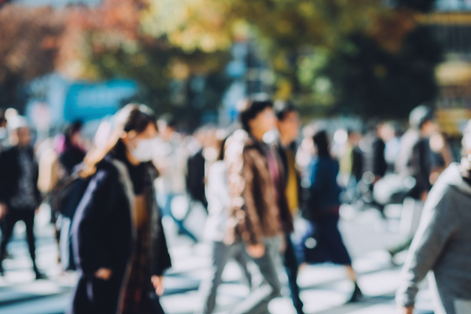 Defocused image of busy commuters crossing street during office rush hours in Shibuya crossroad, Tokyo