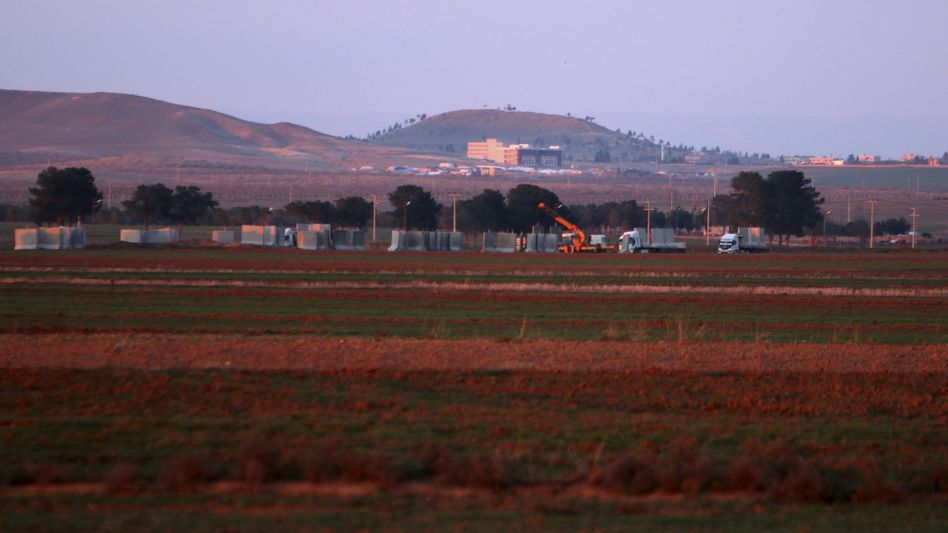 Vehicles carry concrete blocks used in construction of a fence along the Turkish-Syria border in the western countryside of Ras al-Ain, Syria.