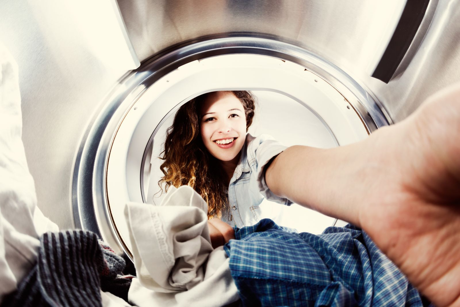 Smiling young beauty loads clothes dryer, seen from inside drum