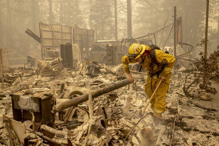 Feuerwehrmann in den ausgebrannten Überresten eines Hauses in Berry Creek, Kalifornien