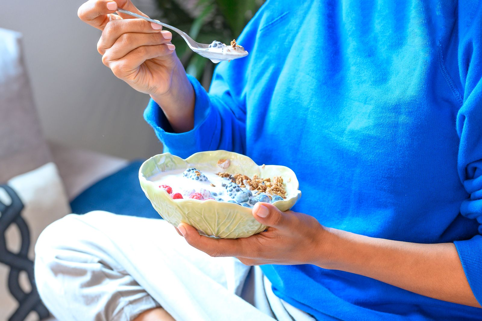 Young woman in fitness clothes having healthy breakfast at home , closeup
